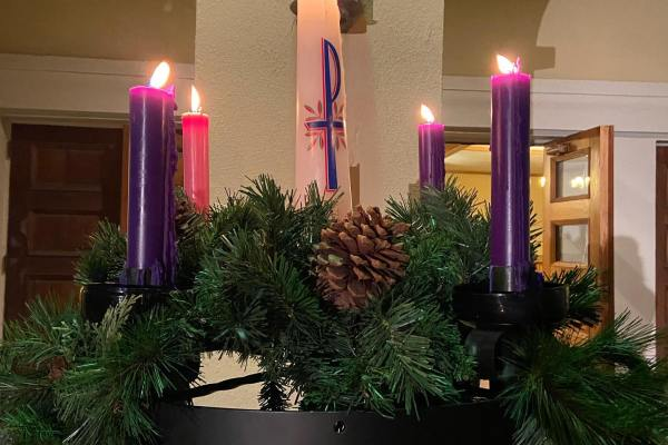 FCC Pomona's Advent evergreen Advent wreath, fully lit on Christmas Eve. 3 purple taper candles and 1 pink candle surround the central white Christ candle.