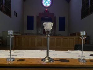 The altar inside the FCC Pomona sanctuary, with two smaller candle stands framing either side of a larger central candle.