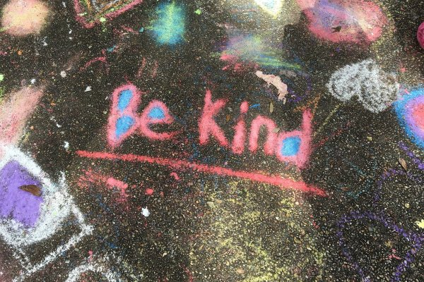 """The words, """"Be Kind"""" are written in pink chalk on black asphalt. Other chalk drawings surround the words as beams of sunlight stream in from outside the frame. The gaps in the b, e, and d of """"Be kind"""" are filled in with bright blue chalk. Image via Pixabay."""