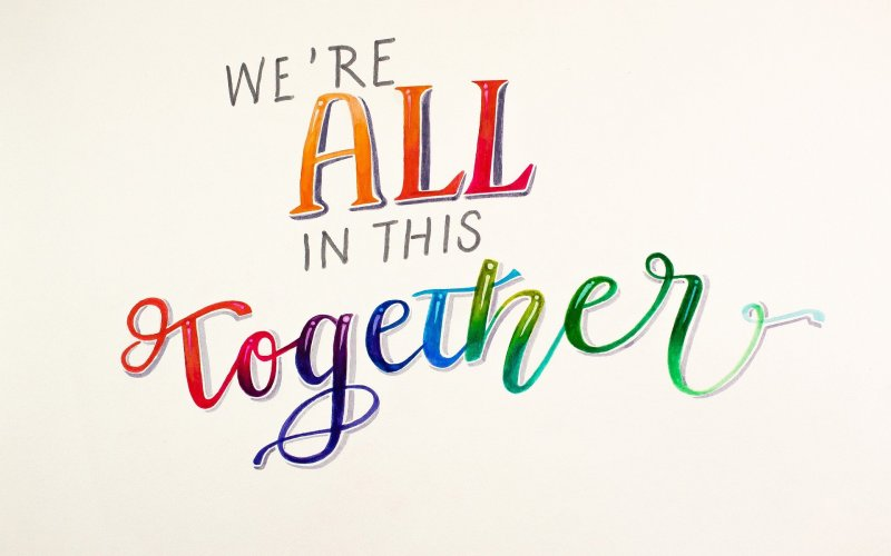 """The words, """"We're ALL in this together,"""" are written across a cream-white background. The words """"ALL"""" and """"together"""" are written in rainbow colors; """"together"""" is also written in cursive. Image via Pixabay."""