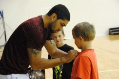 Siva signs a shirt for a camper.
