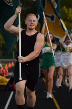 Senior Hunter Hampton carries the school flag after FC scores a touchdown at the football game against Providence on Aug. 28.