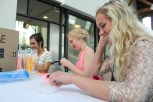 Sophomores Faith Barba, and Emrie Ipsan and junior Olivia Didat, sort glow sticks for the FC prom registration tables. Photo by Kaitlyn Erdman.