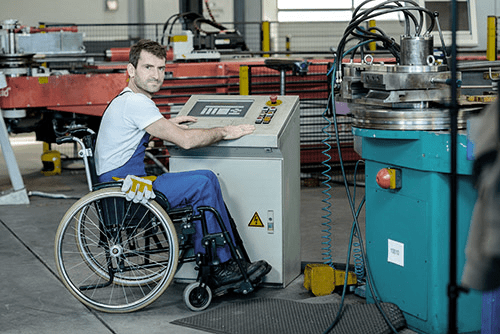 Man in wheelchair working at machine on a factory floor