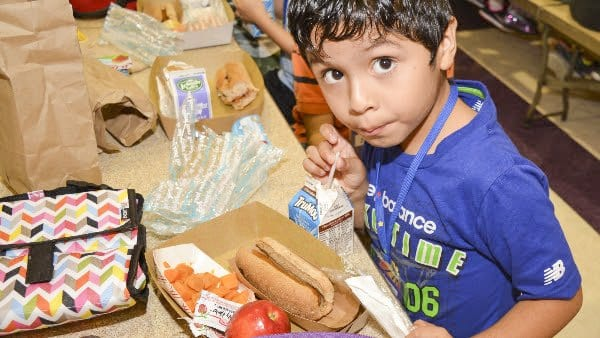 A Falls Church City Public Schools student chows down one of the menu items yesterday:  a hot dog in whole wheat bun, sweet potato cubes and an apple. (Photo: Courtesy of FCCPS Photo/John Wesley Brett)