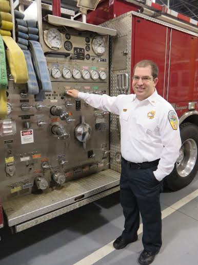 Ian Weston, the president of the Falls Church Volunteer Fire Department, describes the parts of a fire engine at the fire hall at 6950 Little Falls Road in Arlington. (Photo: Patricia Leslie/News-Press)