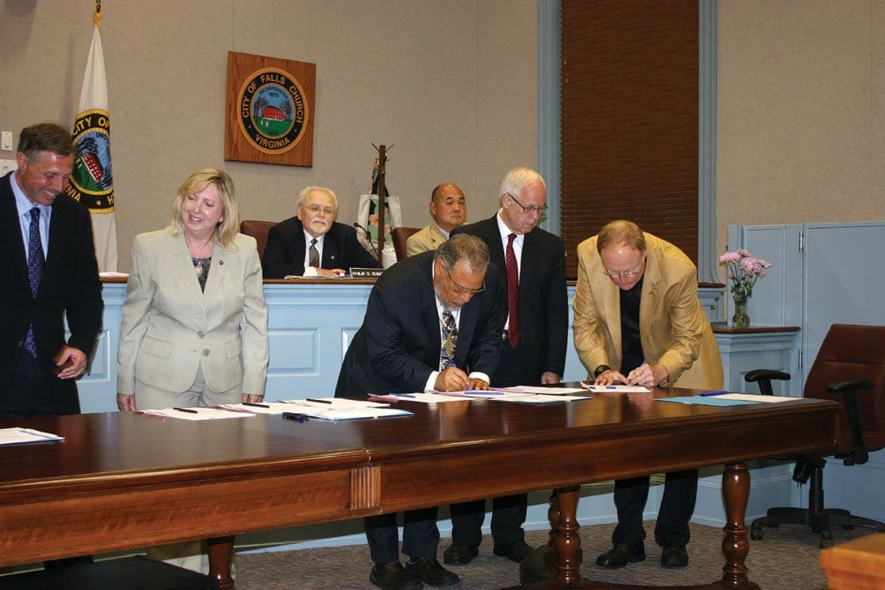 Barry Buschow (right) of the Northern Virginia Regional Park Authority and Tinner Hill Heritage Foundation's Ed Henderson (2nd from left) sign the new proclamation. (Photo: News-Press)