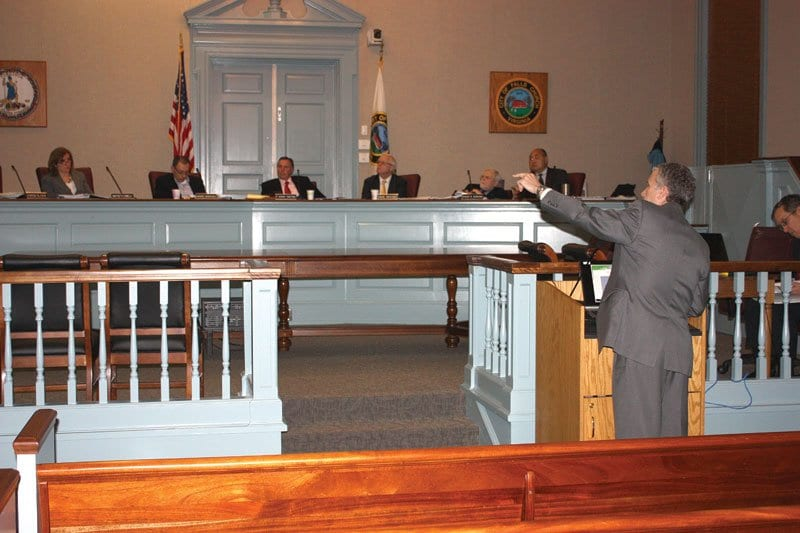 FALLS CHURCH CITY MANAGER Wyatt Shields (foreground) gestures before the City Council to a projected presentation of his Fiscal Year 2015 proposed budget Monday night. The budget deliberation process may become one of the more contentious in years over the next five weeks. (Photo: News-Press)