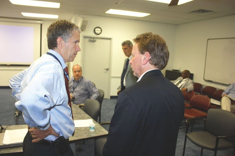 DURING A BREAK in the Falls Church City Council work session Tuesday night, Ed Novak (right), seeking to develop a senior assisted living project on the site of the current Burger King site, chats with F.C. City Manager Wyatt Shields. (Photo: News-Press)