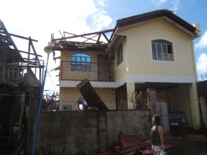 Evelyn Castillo (standing right) looking over her home without a roof