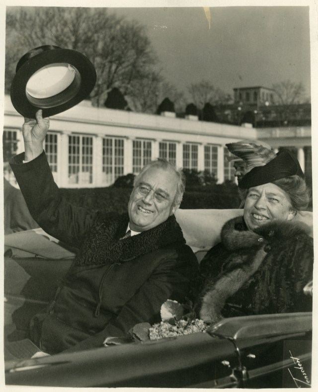 Franklin and Eleanor Roosevelt riding in an open car, returning to the White House from FDR's third inauguration. January 20, 1941.