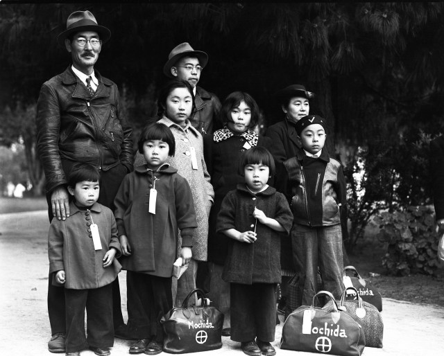 """Members of the Mochida family wait in Hayward, California, for their """"evacuation"""" bus. Each wears an ID tag. The family operated a nursery and five greenhouses in Hayward. Dorothea Lange May 8, 1942"""