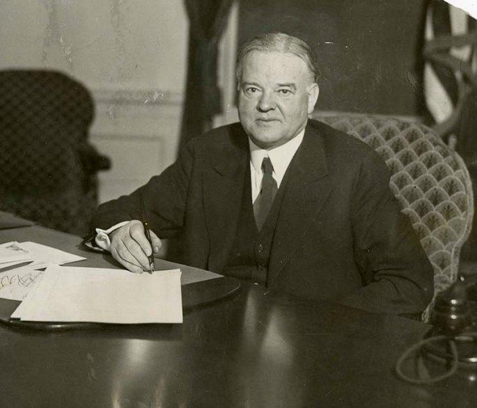 Herbert Hoover sitting at a desk holding a pen