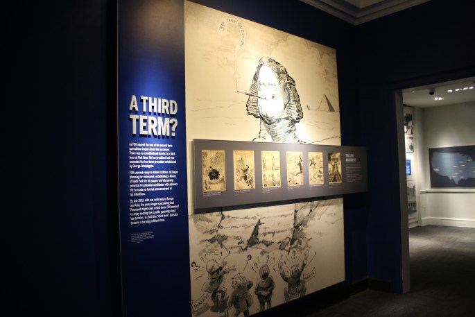 Exhibit panel with paragraph text on the left and cartoon images of FDR as the Sphinx in Egypt on the right
