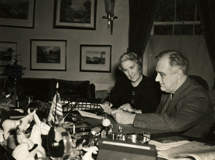 FDR sitting at his desk with Marguerite LeHand next to him
