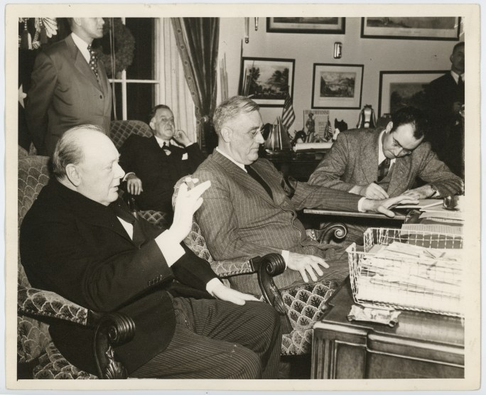 FDR and Winston Churchill sitting at a desk with several other standing and sitting around them