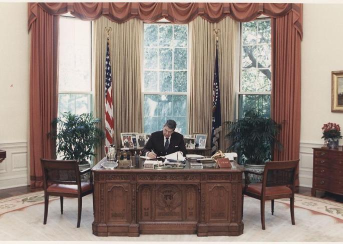 Ronald Reagan sitting at a desk writing on paper