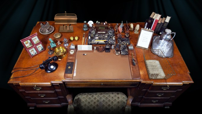 Overhead view of a desk cluttered with many objects