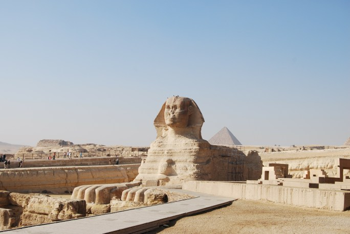 The large stone sculpture Sphinx of Giza in Egypt with a pyramid in the background.