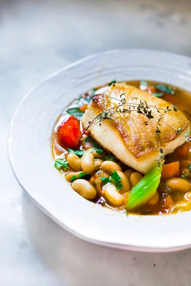 A delicious recipe for Seared Sea Bass over a simple hearty Cannellini Bean Stew. Can be made in 30 minutes. | www.feastingathome.com