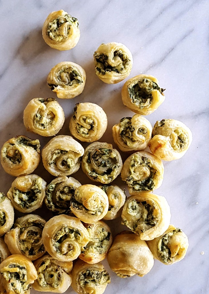 With buttery pastry and gooey cheese, Spinach & Artichoke Pastry Swirls are a delicious bite-size appetizer perfect for any party, from your stylish buffet to a gameday spread. | FeastInThyme.com