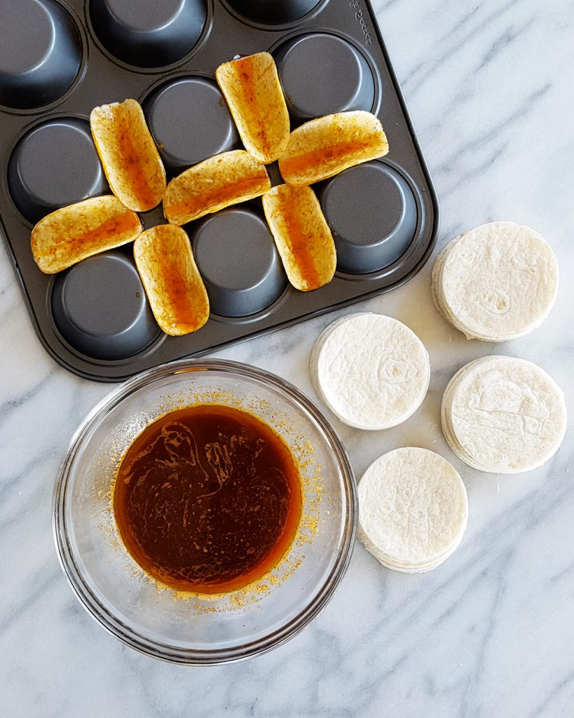 Dipping the mini flour tortilla rounds in soy glaze and setting them in muffin tins. | FeastInThyme.com