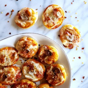 Drizzled with honey, these Mini Prosciutto, Olive, & Fennel Pizza Bites are a salty-sweet combination of classy ingredients and classic #comfortfood – An upscale addition to any #party menu. #pizzaparty #superbowl #gameday   FeastInThyme.com