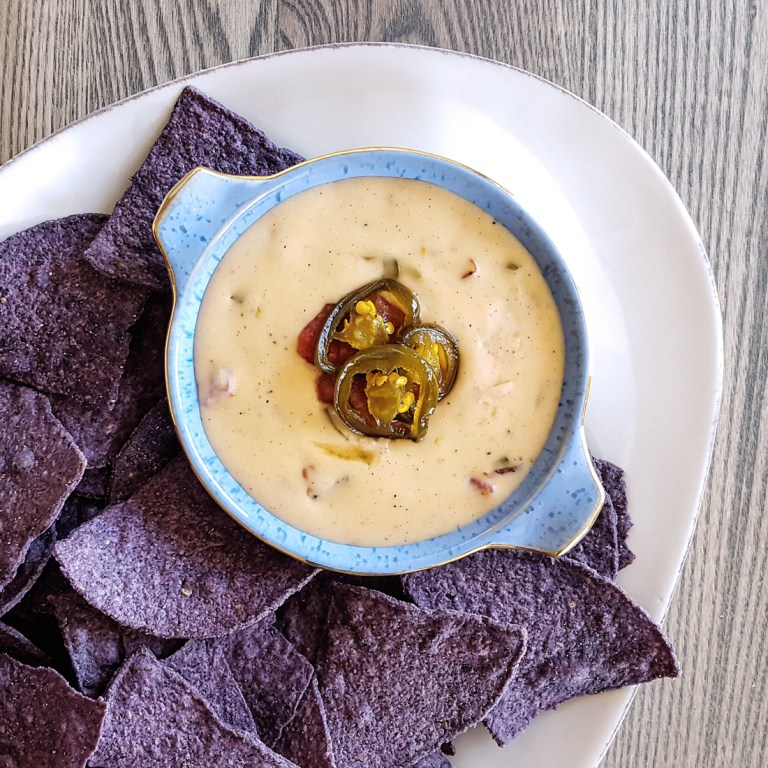 Melty cheddar and jack cheese, roasted tomatoes, and spicy jalapenos make for an easy queso dip that is ready in just 15 minutes! #gameday #snack #cheese #party | FeastInThyme.com