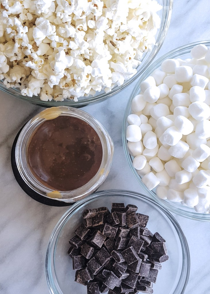 Ingredients for the Salted Caramel Popcorn Bars: Popcorn, caramel sauce, mini marshmallows, and chocolate chunks.
