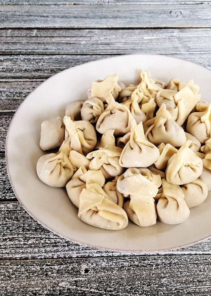 A plateful of prepared Simple Pork & Mushroom Dumplings, ready to be cooked.