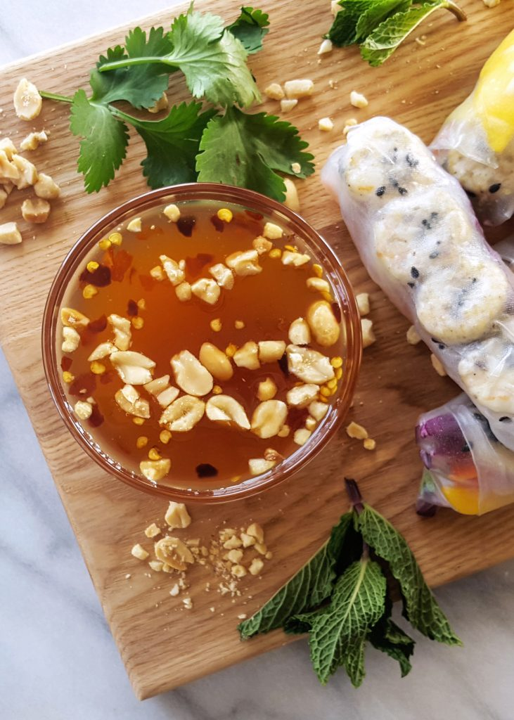 Sweet Thai Chili Sauce on a platter with shrimp summer rolls and crushed peanuts.