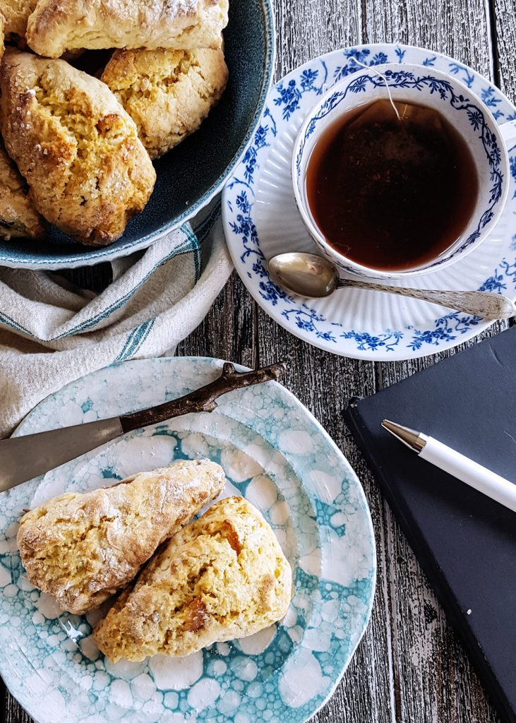A closeup of a personal tea serving, with mini orange scones, a cup of tea, and a writing journal.