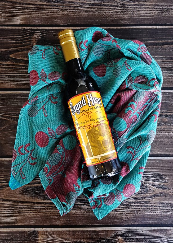 A bottle of Caged Heat Cocktail Syrup laying on a turquoise and cranberry colored dishtowel.