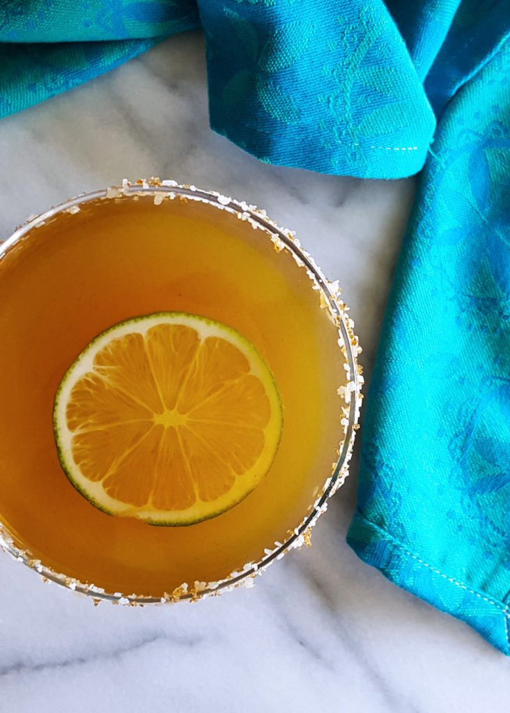 Top view of a Desert Heat cocktail with a lime wheel, surrounded by a turquoise dishtowel.