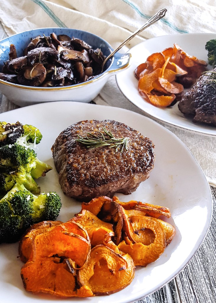 A fully plated meal of pan seared steak tenderloin with wine glazed mushrooms, roasted broccoli, and roasted sweet potatoes. | FeastInThyme.com