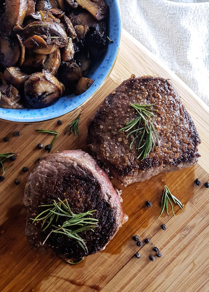 Two pan seared steak tenderloins with black peppercorns, rosemary, and a bowl of sauteed mushrooms. | FeastInThyme.com