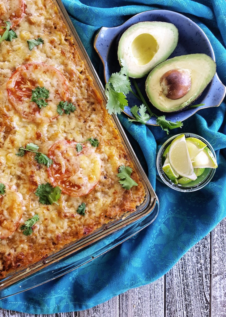 A complete pan of Spaghetti Squash Taco Casserole topped with roasted tomato slices and melted cheese.