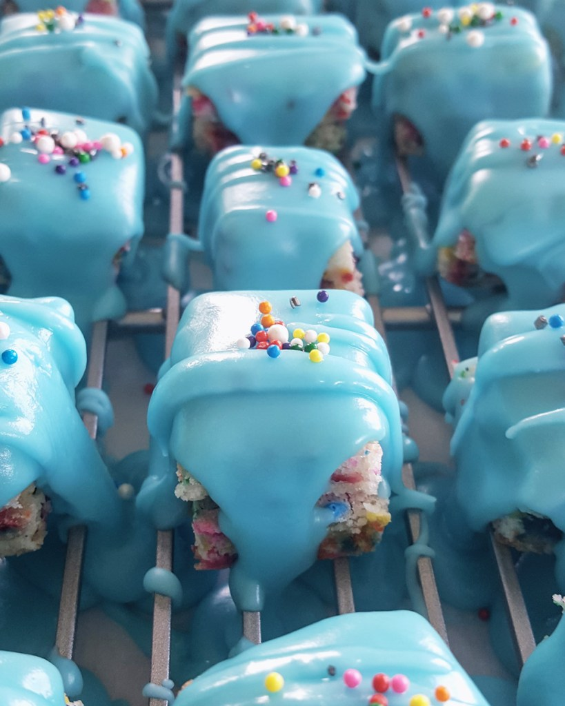 Funfetti Petit Fours on a cooling rack, the fondant icing dripping over them. | FeastInThyme.com