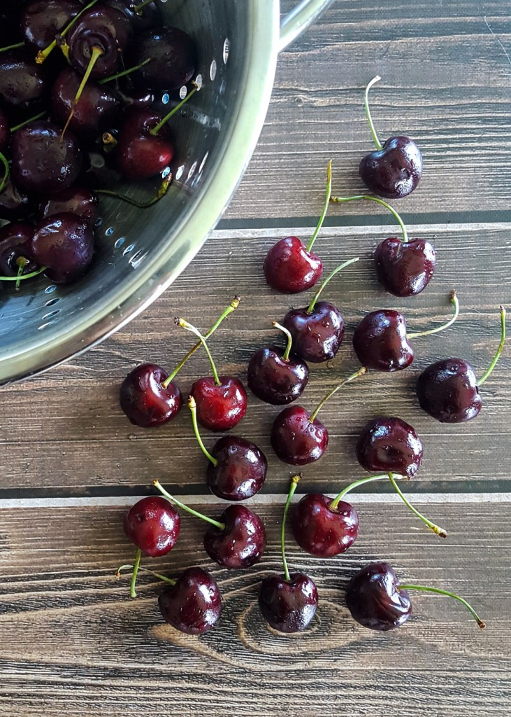 A pile of fresh sweet cherries spread over a wooden surface. | FeastInThyme.com