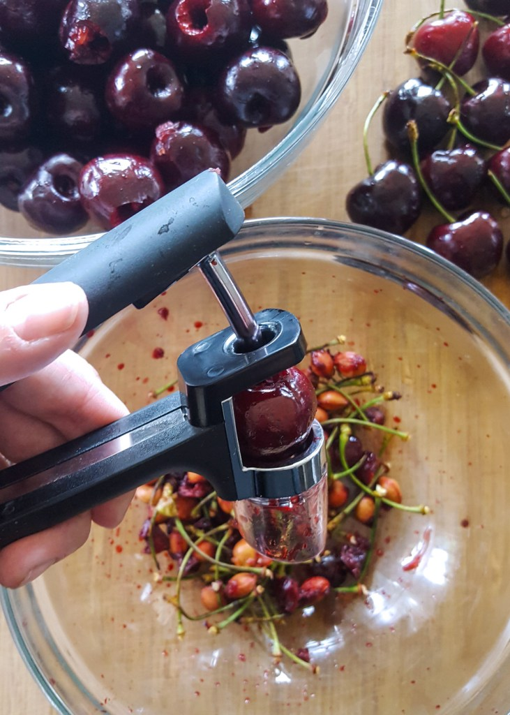 A close-up of a cherry pitter being used with pits, stems, and fresh cherries in the background. | FeastInThyme.com