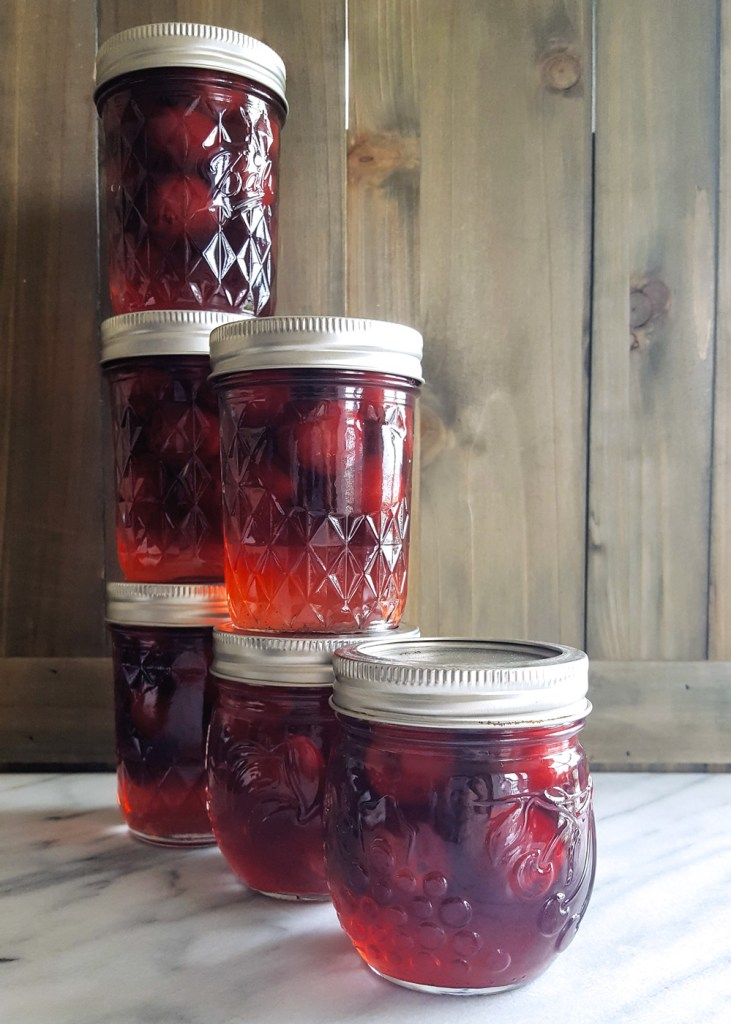 Stacks of bourbon soaked cocktail cherries in jars. | FeastInThyme.com