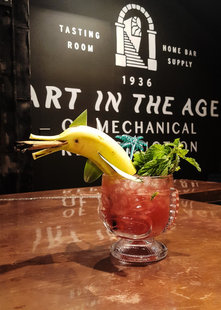 A dolphin garnish made from a banana and pineapple fronds in a tiki cocktail. | FeastInThyme.com