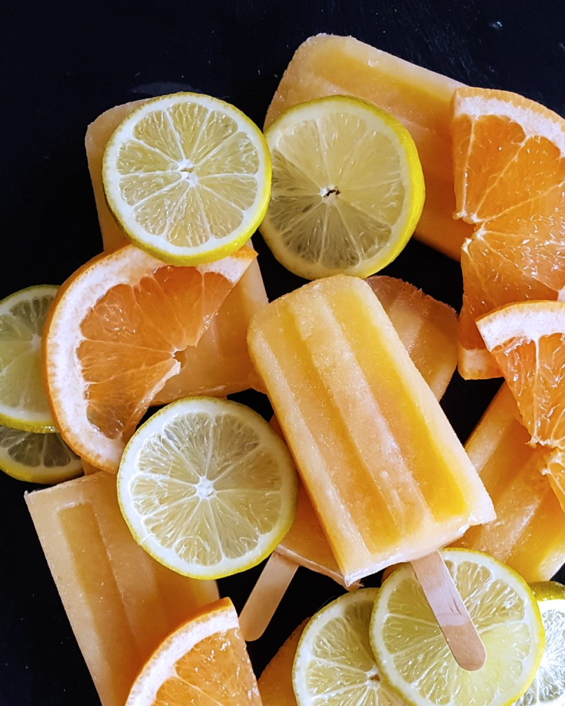 A pile of boozy paloma popsicles surrounded by slices of grapefruit and lime. | FeastInThyme.com