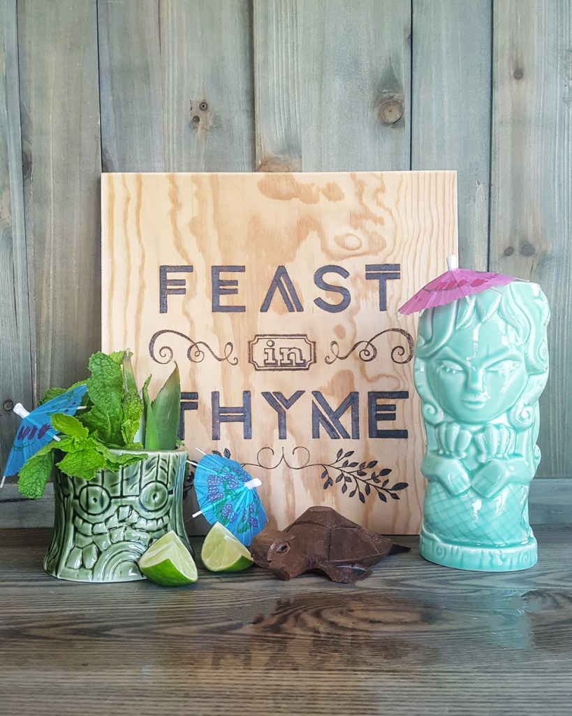 "Tiki mugs and garnishes around a sign that says ""Feast In Thyme"""
