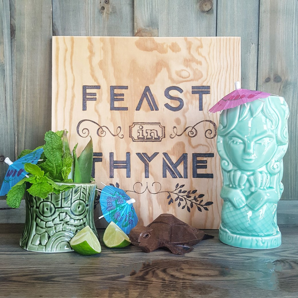 Feast In Thyme signage surrounded by Tiki accessories.