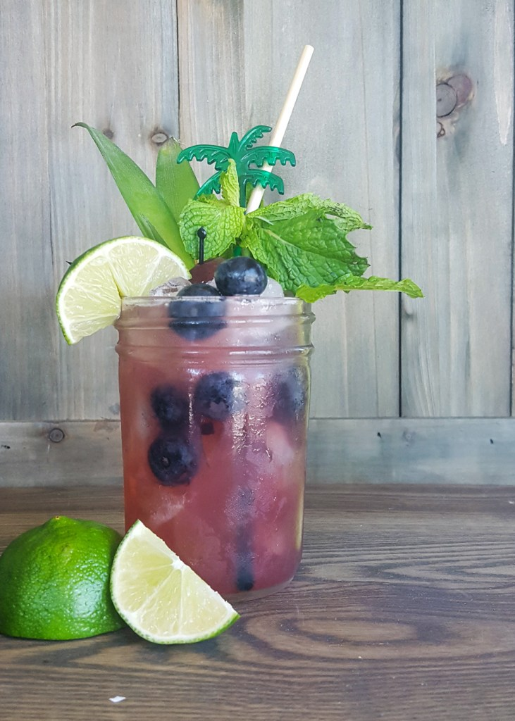 A singular shot of a blueberry rum tiki cocktail, fully garnished. | FeastInThyme.com