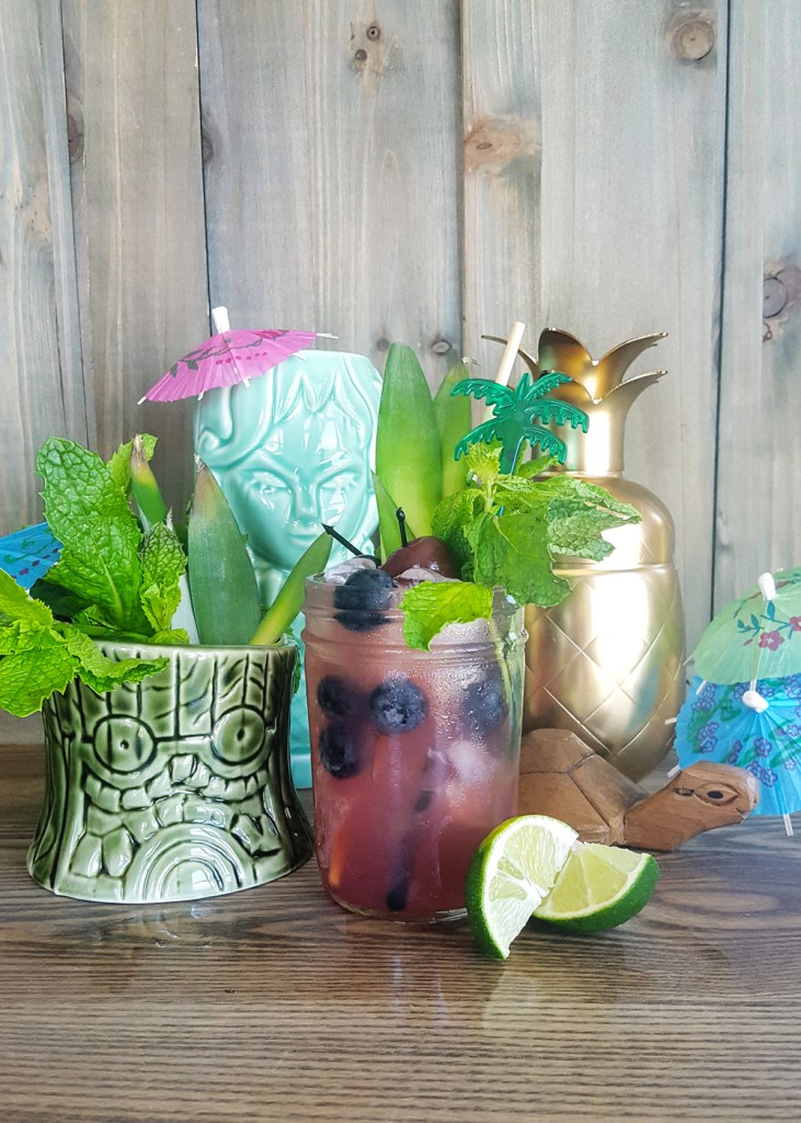 A blueberry rum tiki cocktail surrounded by two tiki mugs, mint leaves, a golden pineapple cocktail shaker, and garnishes. | The Cecaelia | FeastInThyme.com