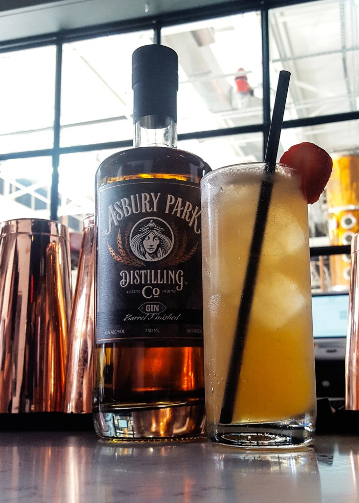 A bottle of Asbury Park Distilling Barrel Finished gin next to a cocktail, with the still in the background. | A Review from FeastInThyme.com