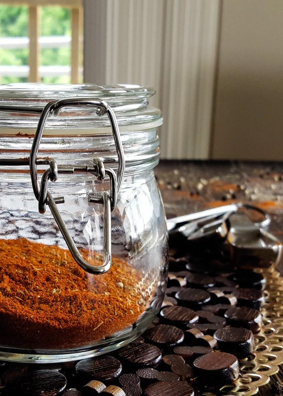 A jar of mixed low fodmap cajun seasoning next to measuring spoons.   FeastInThyme.com