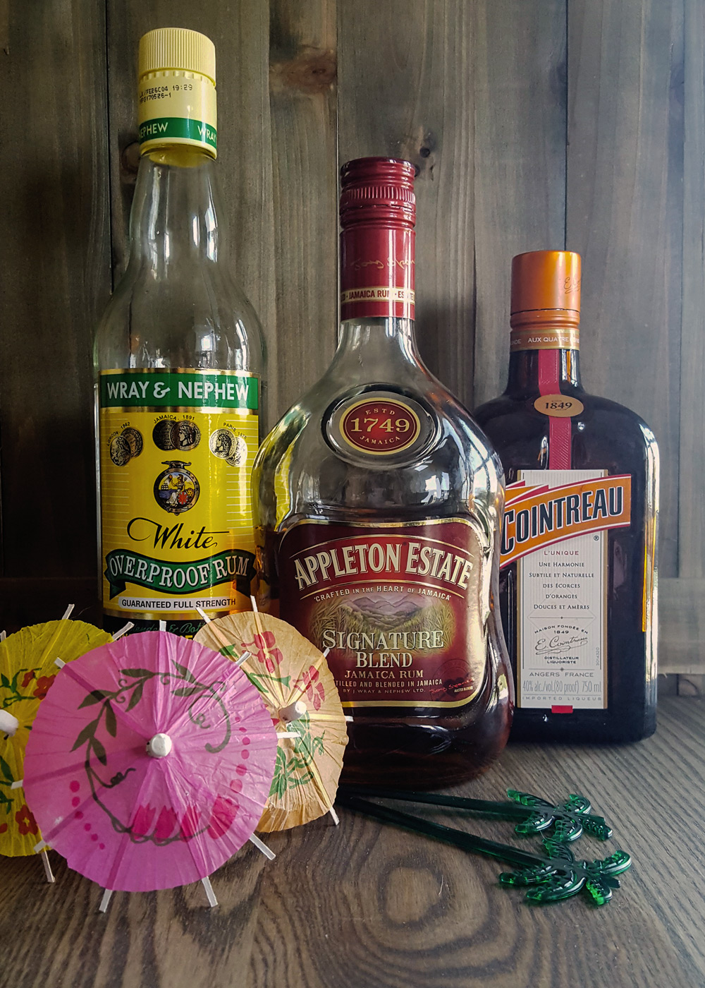 Creating your own Home Tiki Bar is easy with these essential bottles of rum and other liquors! #homebar #diy #tiki #cocktail #rumbar #rum | FeastInThyme.com